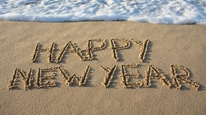 Happy New Year written in the sand at the edge of the ocean.